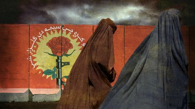 Women walk in front of a blast wall wearing a traditional burka