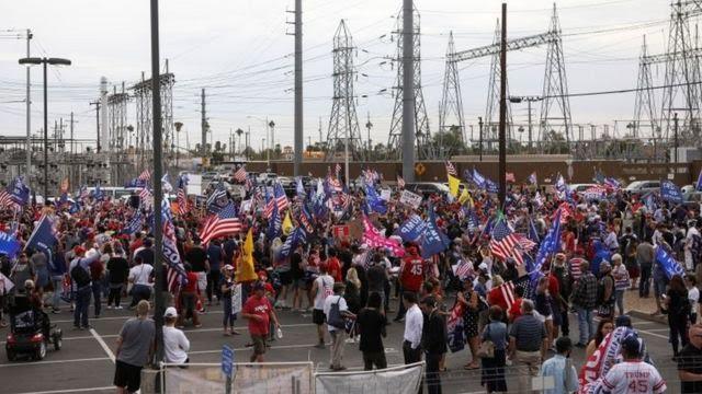 Foto ampla mostra dezenas de manifestantes pró-Trump na rua, várias portando bandeiras