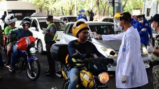 Profissional de saúde mede temperatura de motoqueiro em Curitiba