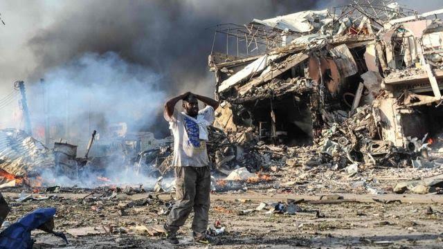 Homem em meio a escombros de prédio depois de explosão