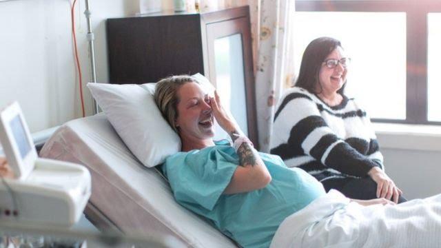 Gestante deitada num leito hospitalar sorri e é acompanha por uma outra mulher ao fundo