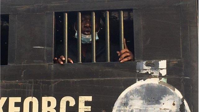 Damilare Adenola inside police van
