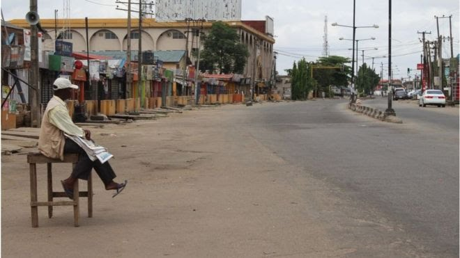 Newspaper vendor siddon for empty street for Lagos during lockdown for March, 20202