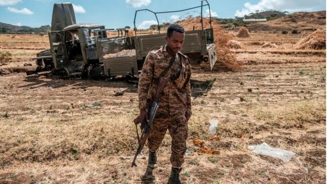An Ethiopian soldier walks in front of a car destroyed by the war