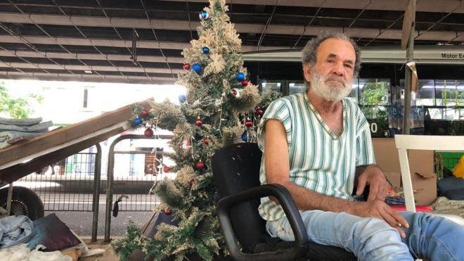 O carroceiro Ubiratan Cipriano e, ao fundo, sua árvore de Natal embaixo do Minhocão