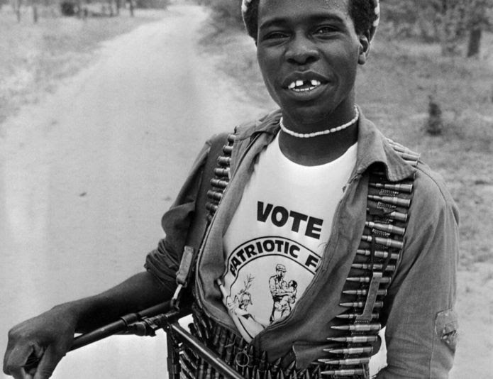 A fighter who supports the Patriotic Front carrying bullets and a machine gun, smiles during the general elections, March 04, 1980 in Lupane camp