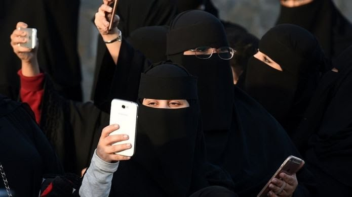 Women dressed in niqab holding phones