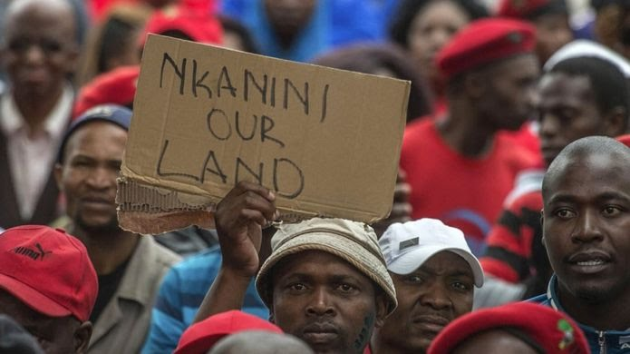"South African opposition protest in 2016 with someone holding up a sign reading ""Nkanini our land""."