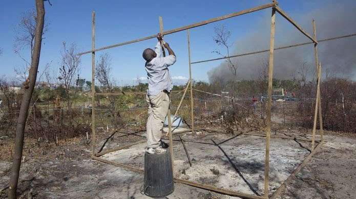 A man builds a shack after he joined people from a neighbouring informal settlement in Khayelitsha, in occupying land allegedly belong to the South African national weapons manufacturer, DENEL on April 7, 2015.