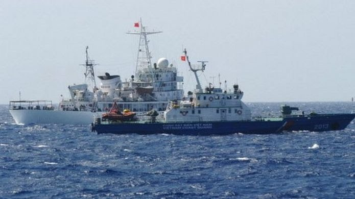 This picture taken on 14 May shows a Chinese coast guard ship (back) sailing next to a Vietnamese coast guard vessel (front) near China's oil drilling rig in disputed waters in the South China Sea.