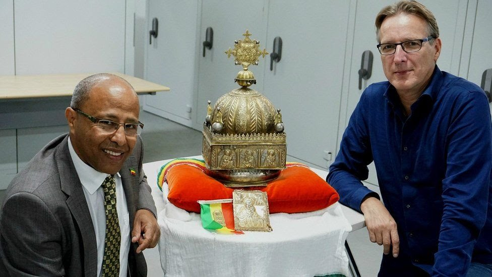 Sirak Asfaw and Arthur Brand sit next to the crown, which depicts the Holy Trinity and Christ's twelve disciples