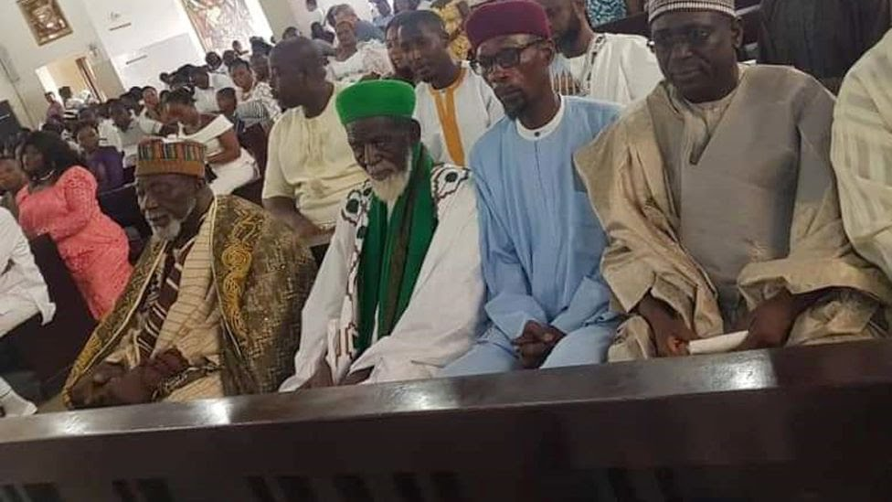 Sheikh Osman Sharubutu (C), in green, sitting in a pew at the Christ the King Catholic Church in Accra, Ghana