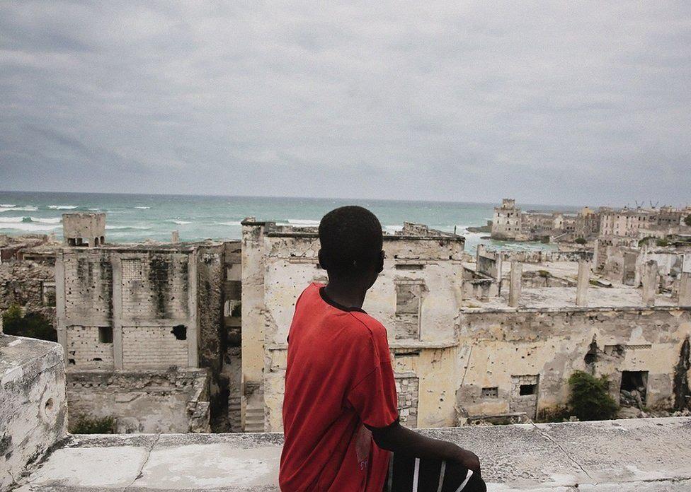 Boy looking over ruined buildings