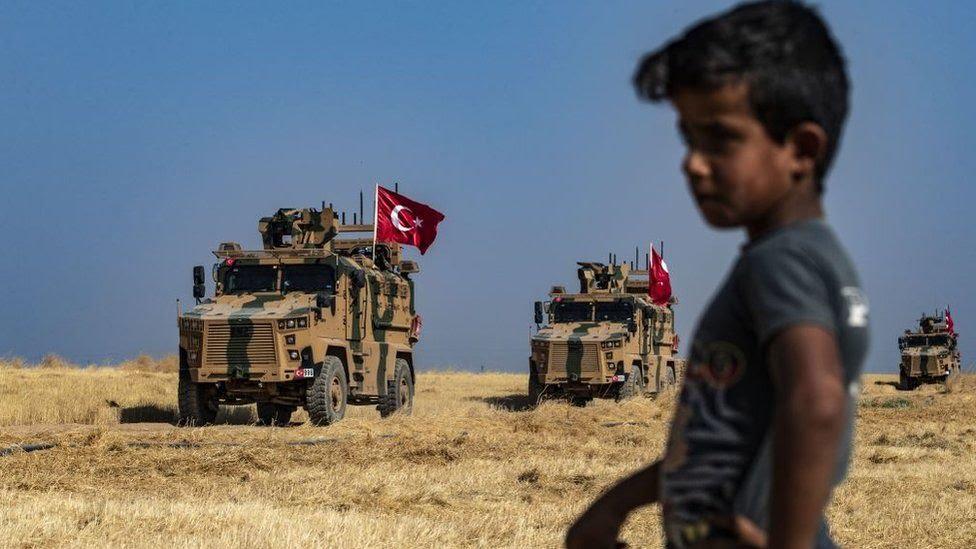 Nio en la frontera de Turqua y Siria con tanques militares en el fondo