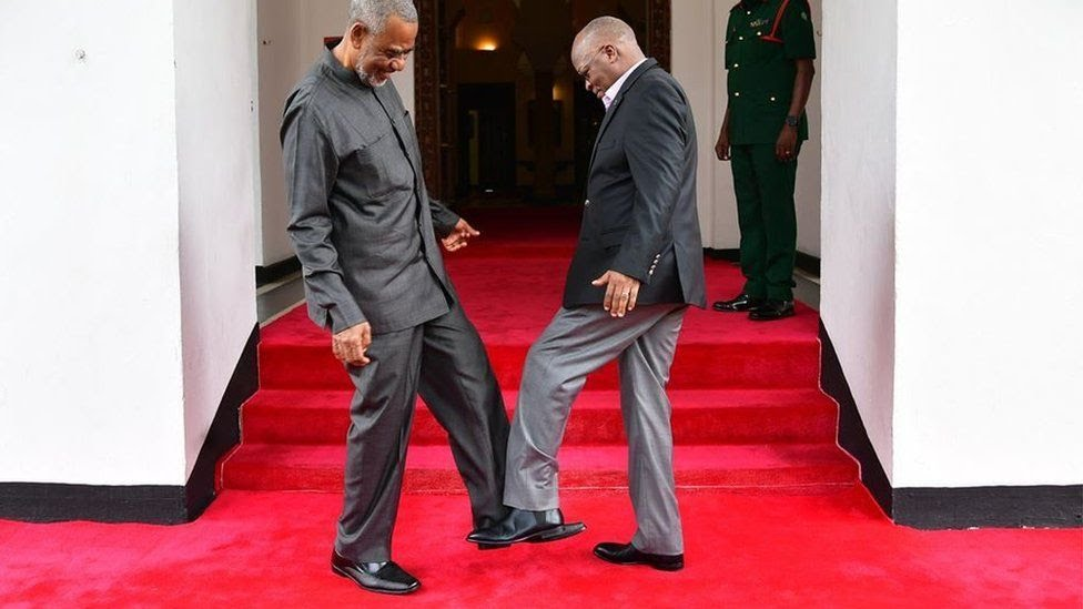 Tanzanian President John Magufuli (R) greets Tanzanian opposition politician Maalim Seif Sharif Hamad (L) by tapping his feet against theirs to avoid themselves from coronavirus in Zanzibar, Tanzania on March 03, 2020