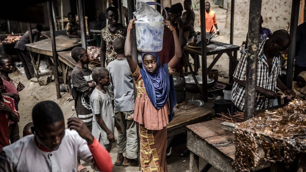 A girl selling water waits for costumers at a market