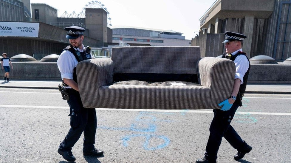 Officers carry sofa