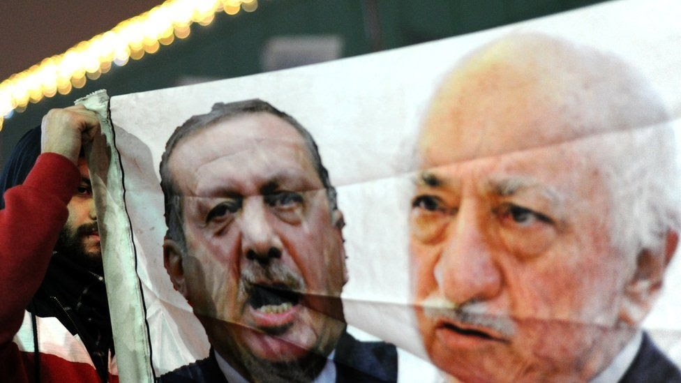 A Turkish protester holds up a banner with pictures of Recep Tayyip Erdogan and exiled Turkish cleric Fethullah Gulen during an anti-government demonstration
