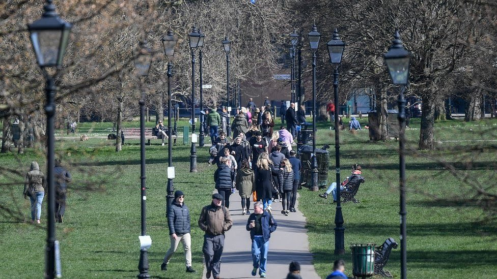 People are seen walking on Clapham Common on March 22, 2020 in London, United Kingdom.