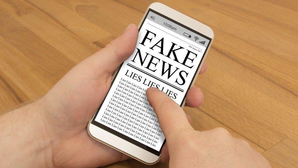 Pantalla de un teléfono móvil con una referencia a las noticias falsas y las mentiras