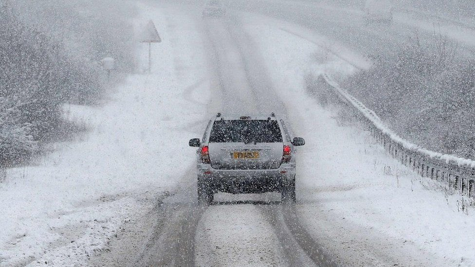 A car is driven along a slip road leading to the snow and sleet-covered A34 road a near Chievely, in Berkshire, west of London