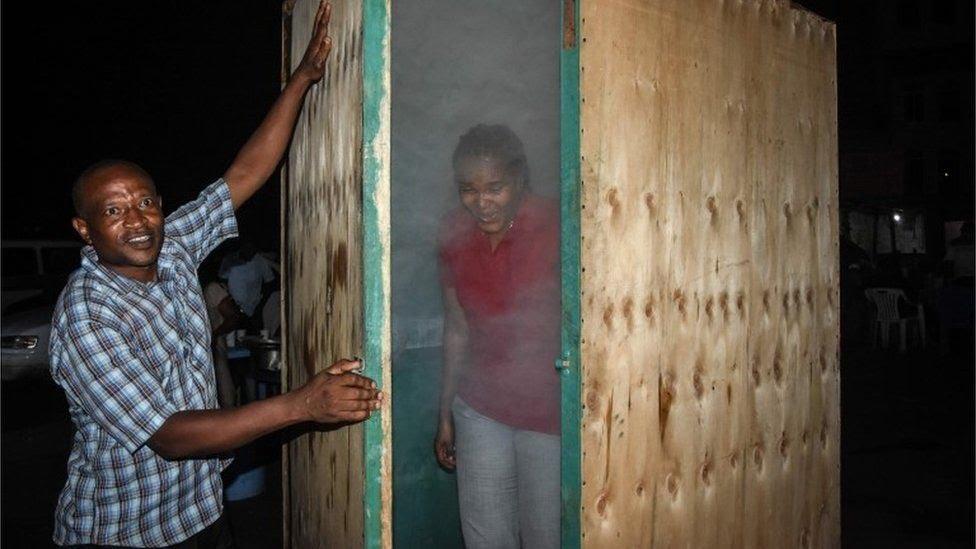 A woman leaves the steam inhalation booth installed by Tanzanian herbalist Msafiri Mjema in Dar es Salaam, Tanzania, on May 22, 2020 after using the treatment as a preventive measure against COVID-19 coronavirus