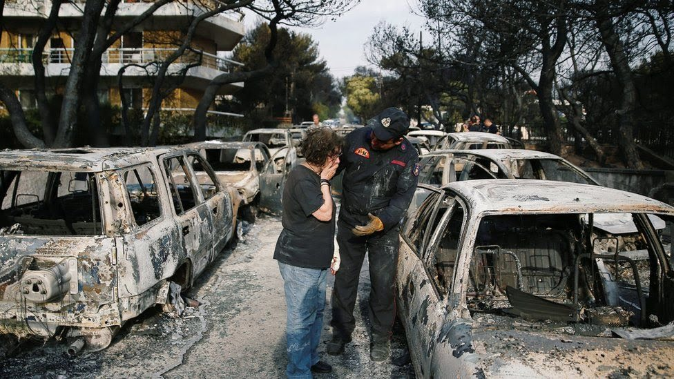 A woman reacts as she tries to find her dog, following a wildfire at the village of Mati, near Athens, Greece July 24, 2018