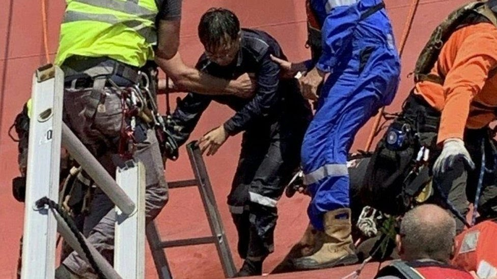 A US Coast Guard handout shows salvage and rescue teams extracting a crew member of the overturned 656-foot vehicle