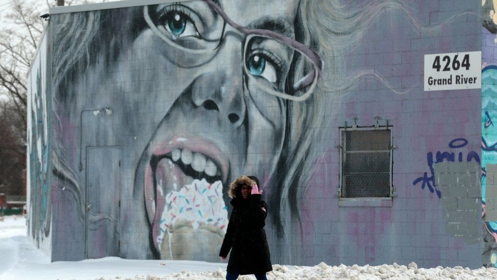 A woman walks past a mural of a woman eating ice cream