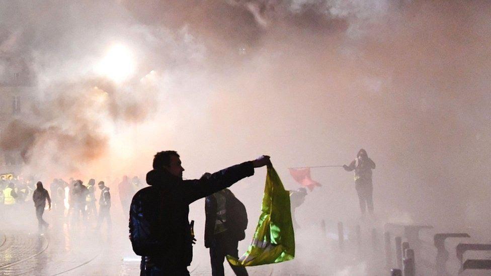 """A protester holds a yellow vest a smoke billows over during a """"Yellow Vest"""" anti-government demonstration outside the city hall of Bordeaux, south-western France, on 12 January 2019"""