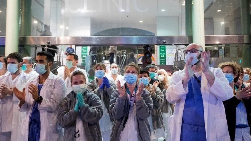 Healthcare workers react during a collective appreciation clapping event in Spain