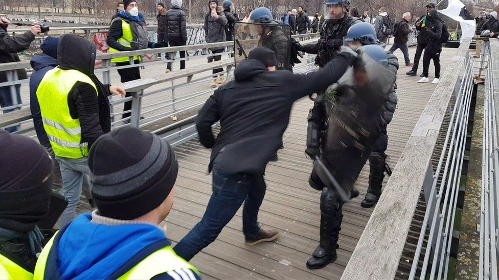 "A man in a boxing stance fights riot police during a demonstration by ""Gilets Jaunes"" anti-government protesters on a bridge leading to the National Assembly in Paris on January 5, 2019"