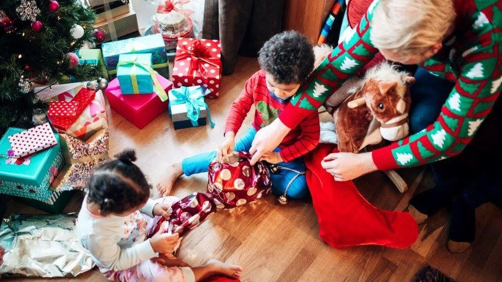 Grandfather and kids open presents