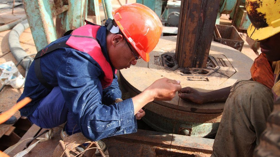 A Chinese technician with China Railway Major Bridge Engineering Company Limited (MBEC), Li Shaoxun, measures the depth of one of the piers on the construction site of a bridge at Kurasini area in Dar es Salaam on March 23, 2013