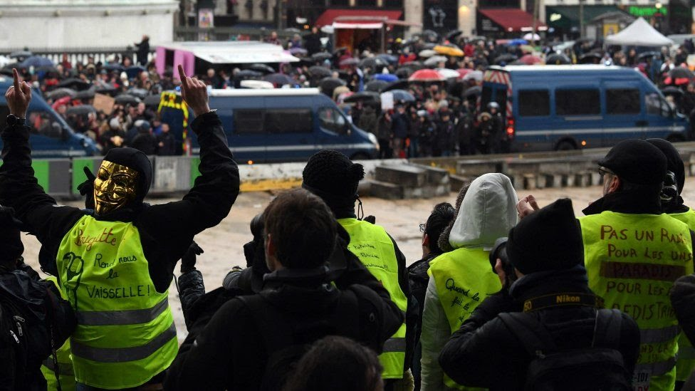 Yellow vests watch as red scarves march through Paris. 27 Jan 2019