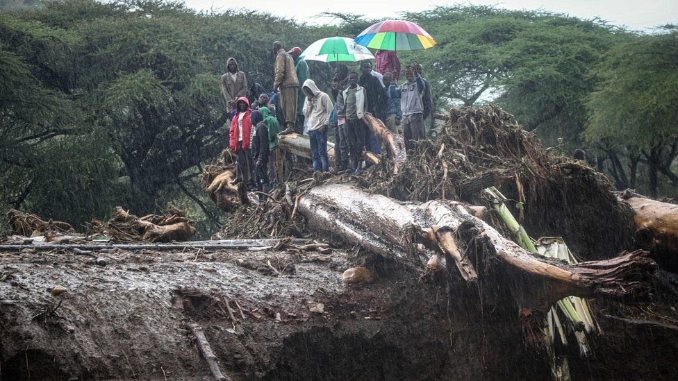 People stand on debris blocking a highway on a bridge after the River Muruny burst its banks in West Poko, Kenya - November 2019