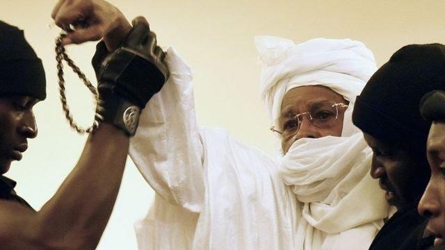 Hissène Habré wahoze ari umunyagitugu muri Tchad (uri hagati), arinzwe n'abarinzi ba gereza yerekezwa mu rukiko mu iburanisha rya mbere mu rubanza rwe i Dakar mu rugereko rwihariye rwa Afurika, ku itariki ya 20 y'ukwa karindwi mu 2015.