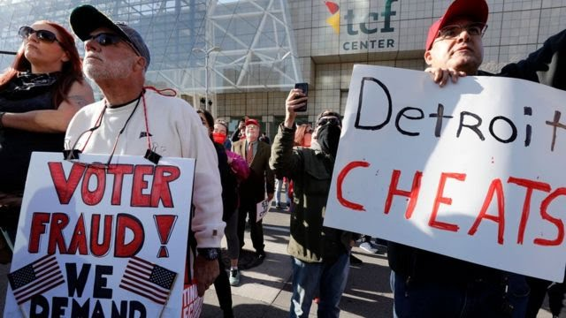 """Two male protesters in Michigan hold signs claiming voter fraud. One reads """"Voter fraud"""" and other other """"Detroit cheats""""."""