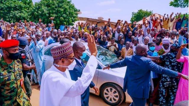 Crowds waving at President Buhari