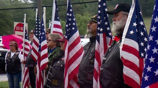 Veteranos enfileirados em cerimônia, ao lado de bandeiras dos EUA