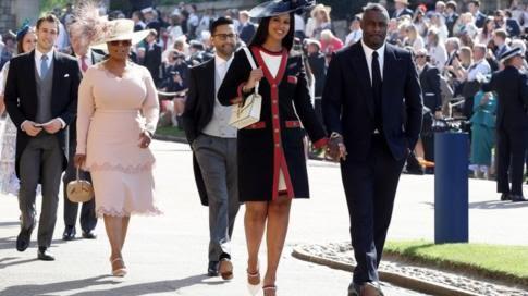 US TV star Oprah Winfrey, wearing pink, and British actor Idris Elba arrive at the chapel